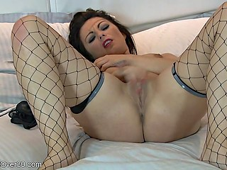 Dark-haired woman in fishnet stockings has to overcome excitement by masturbation