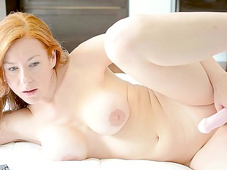 Pale-skinned redhead with big tits brings a pink dildo into play to reach a bright orgasm
