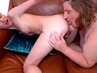 Dutch women with hairy pussies smile and undress to fuck each other on the leather couch