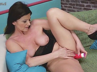 Dark-haired old minx uses a red vibrator to bring herself to orgasm on the green couch