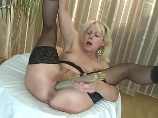 Light-haired old woman in stockings uses a dual-ended dildo to satisfy excited vagina