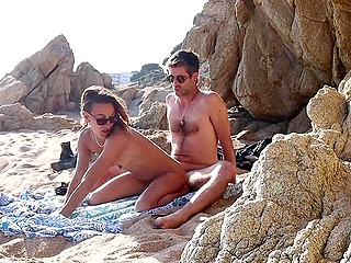 Lovers come to the beach where the man fucks the lady with sunglasses among the stones