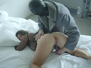 Busty Latina stunner pisses on bed after having her bald pussy toyed by strange man in latex mask