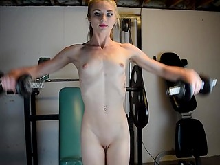Muscles stand out over thin skin when athlete girl trains and poses naked in the gym