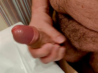 Man with a hairy groin likes silently masturbating and pouring sperm into the sink in solo video