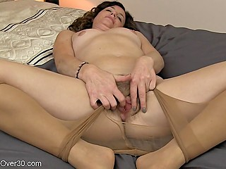 Slim MILF in sexy pantyhose lies naked on the bed and unhurriedly fingers own hairy peach