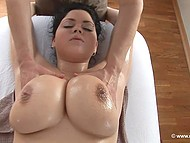 Lucky masseur oils up and touches massive natural boobs belonging to stunning brunette