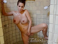 Big-boobied goddess with a navel piercing combines taking a shower with pussy fingering