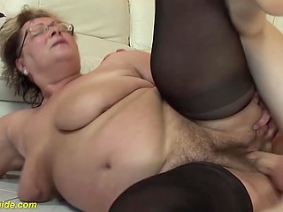 Hairy pussy of fat granny in stockings receives injection of pleasure with the man's penis
