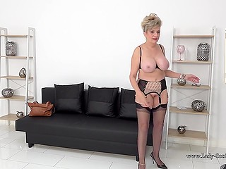 Mature looks at reflection and undresses enjoying the alluring view of her own big breasts